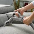 Dùng máy hút bụi để loại bỏ những hạt bụi bẩn trên bề mặt ghế