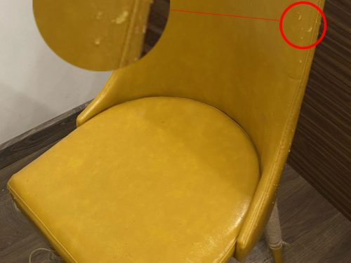 Chiếc ghế ăn màu vàng nghệ bị mèo cào thủng nhiều lỗ