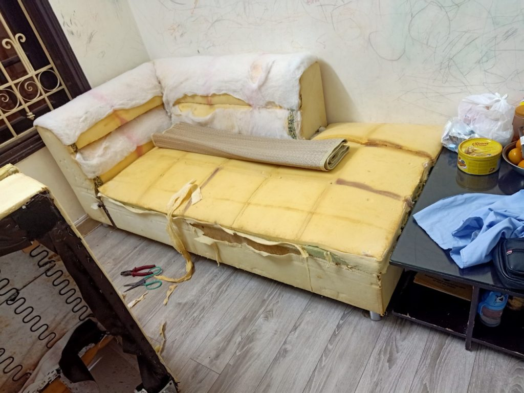Nhân viên Vinaco đã tháo lớp vỏ cũ chuẩn bị bọc lớp da mới thay cho ghế sofa góc tại nhà anh Nam, phường Mỹ Đình